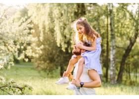 公园里微笑的小女孩骑在父亲的肩膀上_2572845