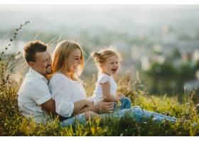 美丽的夏日幸福的父母和他们的小女儿在草_2913962