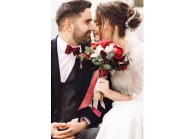 迷人的新娘和新郎坐在外面的长凳上温柔地抱_2612626