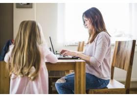 站在母亲面前用笔记本电脑工作的女孩_2602102