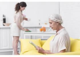资深妇女坐在沙发上看书坐在妇女保洁桌前_2698344