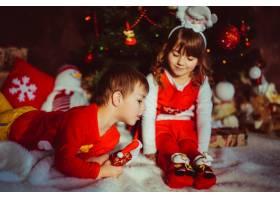 身穿红色衣服的孩子们坐在圣诞树前_1617064