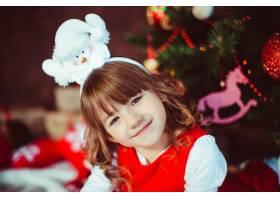 穿着红色连衣裙的小女孩坐在圣诞树前_1617066