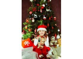 穿着红色连衣裙的小女孩拿着礼品盒坐在圣诞_1617061