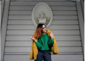 身穿花哨黄色毛皮夹克的时装模特在外面的白_2447275