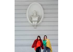 身穿黄红相间毛皮大衣的时装模特在白墙前摆_2447271