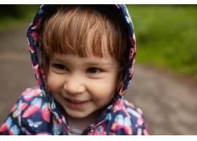 穿着雨衣的滑稽小女孩站在绿色公园里_2914003