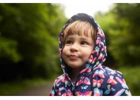 穿着雨衣的滑稽小女孩站在绿色公园里_2916395