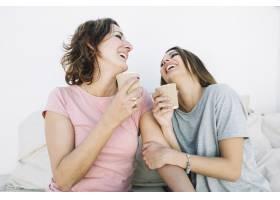 笑着的女人在沙发上喝热饮料_2172340