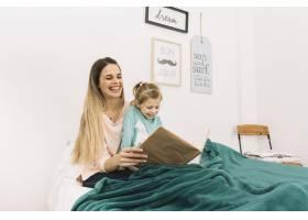 笑着的母女俩盖着毯子看书_2857152
