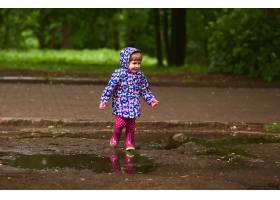 雨后穿着橡皮靴的小女孩在游泳池里散步很_2916406