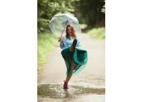 雨后身着绿色短裙的年轻美女穿着口香糖靴_2916344