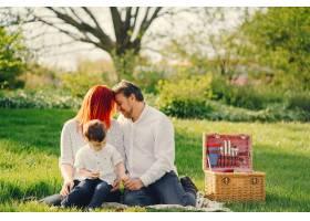 红发妈妈穿着白色上衣和她的帅哥坐在草地上_2611430