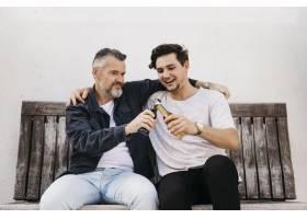 父子俩坐在长凳上喝啤酒_2303201