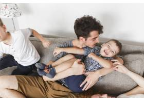 父母和他们的儿子在沙发上玩得很开心_3134263
