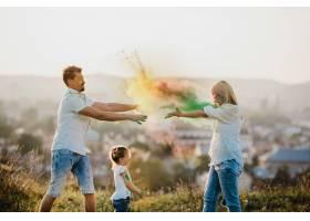 爸爸妈妈和他们的小女儿在草坪上玩五颜六色_2913971
