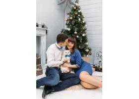 男人和女人在圣诞树前互相拥抱与白色小猫_2446705