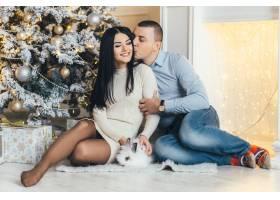 男人和美女帶著一只小兔子在閃閃發光的圣誕_2437870