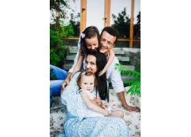 漂亮的父母和他们的小女儿坐在外面的脚步声_1617261