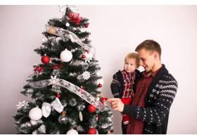父亲和儿子在圣诞树旁_1603621
