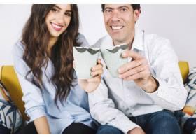 父亲和女儿在沙发上拿着杯子_2247704