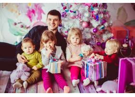 父亲在圣诞树旁拥抱他的孩子_1617111
