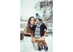 母子俩坐在雪人旁边_2446788