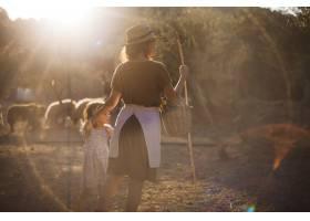 母亲和女儿在农场里提着篮子和棍子_3149933