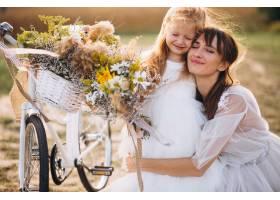 母亲带着她的孩子穿着漂亮的衣服骑着自_2858987