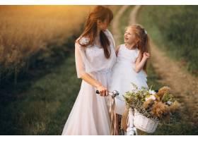 母亲带着她的孩子穿着漂亮的衣服骑着自_2858988