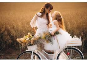 母亲带着她的孩子穿着漂亮的衣服骑着自_2858990