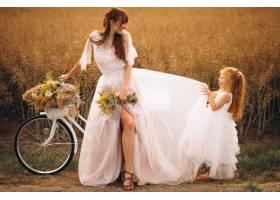 母亲带着她的孩子穿着漂亮的衣服骑着自_2858992