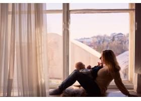 母亲抱着儿子坐在窗台上_2438252