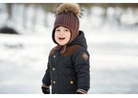 戴着滑稽冬帽的迷人小男孩在公园摆姿势_2437545