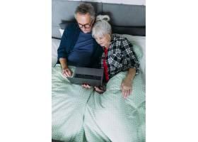 拿着笔记本电脑躺在床上的老年夫妇的俯视图_2284875