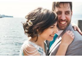 新娘和新郎温柔地坐在水面上的海滩上拥抱着_2631431