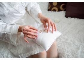 新娘手持带结婚戒指的枕头_1621016