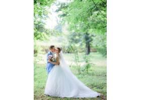 新郎与新娘站在绿色公园亲吻新娘温柔的脸颊_2612793