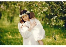 年轻漂亮的怀孕女孩穿着白色长裙怀里抱着_2534539