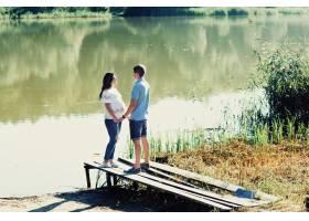 年轻的准夫妇站在绿河边的桥上_1620652
