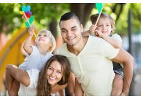 年轻的家庭和孩子们玩五颜六色的风车_1632126