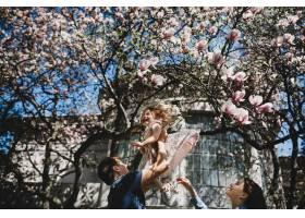 幸福的年轻父母带着一个小女儿站在外面盛开_2914137