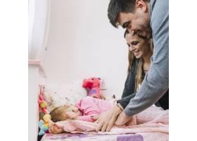 幸福的父母带着女儿在床上散步_2900773
