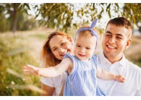 幸福的爸爸妈妈抱着小女儿站在傍晚的阳光下_2437856