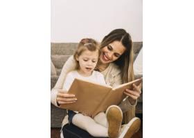 开朗的母亲在沙发旁给女儿读书_2925027