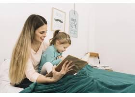 微笑的女人在床上给女儿读书_2857142