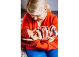 微笑的母亲怀里抱着戴着红帽子的新生儿_1617093