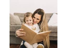 微笑的母女俩在沙发旁看书_2848775