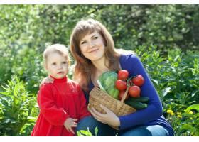 快乐的女人和带着蔬菜的女婴_1584036