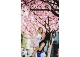 年轻漂亮的妈妈抱着可爱的小女儿站在盛开的_2914124